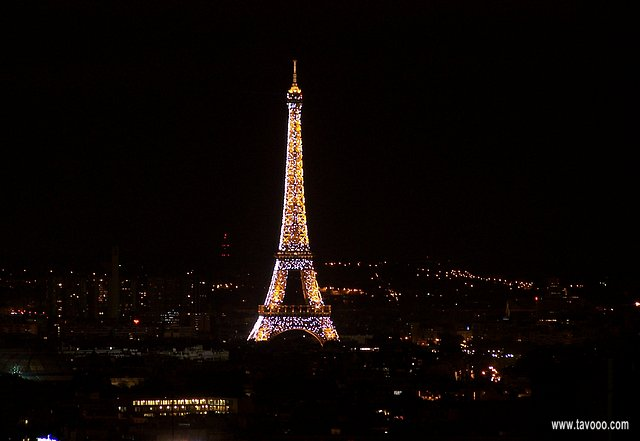 At night the Eiffel tower sparkles, lit by thousands of bright blinking lights.
